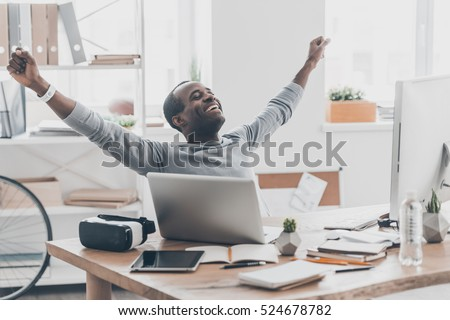 Success achieved! Beautiful young African man gesturing and smiling while sitting at the desk in creative office Royalty-Free Stock Photo #524678782