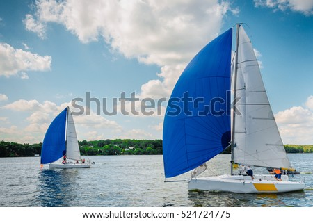 Sailboat. Yachts on the background of blue sky. Sailing yacht race. Boat with big blue spinnaker sail, picture with space for text or logos