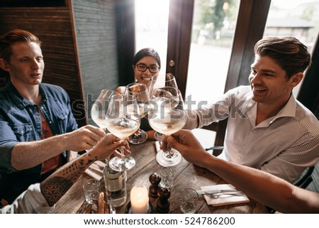 Indoor shot of young friends toasting with a glass of wine at a restaurant. Group of men and women enjoying a dinner at restaurant. #524786200