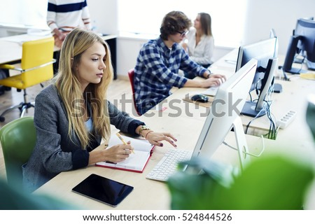 Female international student translating business article for upcoming exam using online programs and computer and fast 4G wifi connection during training lesson in modern university workshop