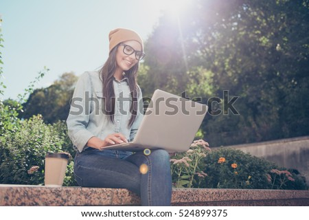 Happy hipster young woman working on laptop in the park #524899375