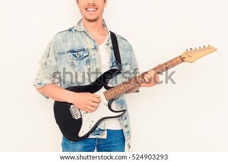 Close up of young rocker with beaming smile and electric guitar. #524903293