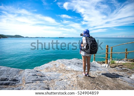 Woman or girl photographer journalist traveling at nature mountain on the sea taking pictures scenery of the beautiful beach and blue sky.  Travel Concept