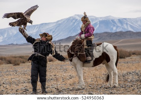 Kazakh Eagle Hunters in traditionally wearing typical Mongolian dress culture of Mongoliashe Rider horse on Altai Mountain background  at Bayan UlGII, MONGOLIA #524950363