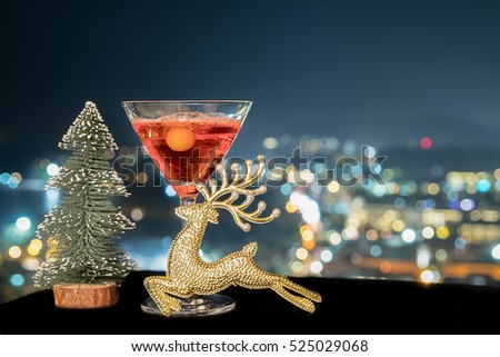 A glass of cocktail margarita or rose wine with bottle of decoct over light city blurred background, Christmas festive celebration. End of the year, Welcome to New Year 2020. Good long holiday start. #525029068
