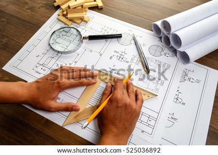 Mechanical engineer at work. Technical drawings. Paper with technical drawings and diagrams. Royalty-Free Stock Photo #525036892