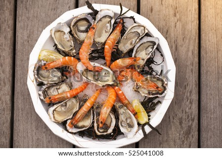 Plate with seafood - oysters and shrimps on wooden background. Toned with sepia colors. Seafood concept.  #525041008