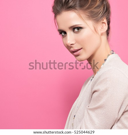Closeup portrait of beautiful young woman with a smile. Light makeup and sensual look. Stylish appearance, bright blouse. Delicate pink background