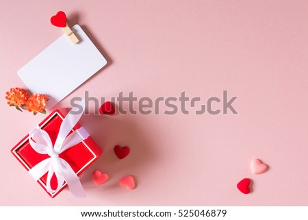 Valentine day composition: red gift box with bow, credit / visiting card template with clamp, spring flowers and small hearts on light pink background. Top view. #525046879