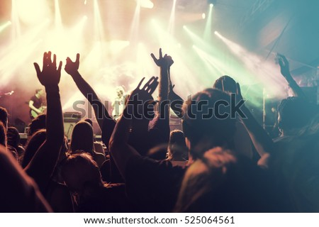 Crowd at concert - Cheering crowd in front of bright colorful stage lights Royalty-Free Stock Photo #525064561