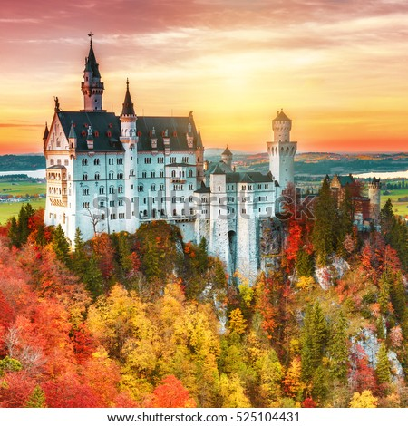 Famous Neuschwanstein castle at amazing sunset sky background, yellow and green leaves trees at foreground. Fantasy art postpruduction. Square format photography. Germany, Fussen.