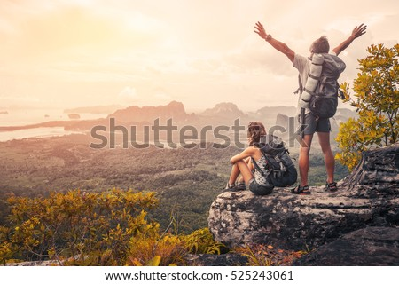Hikers with backpacks relaxing on top of a mountain and enjoying the view of valley at sunset Royalty-Free Stock Photo #525243061