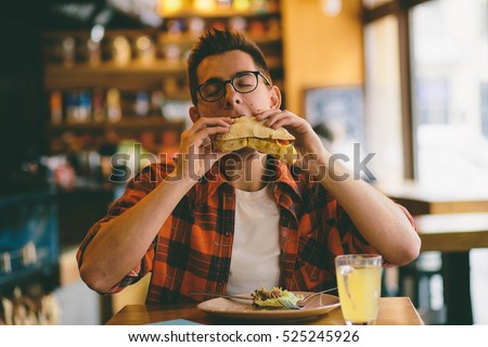 Man is eating in a restaurant and enjoying delicious food #525245926