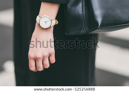 close up fashion details, young business woman holding her black elegant bag. wearing golden and white watch. ideal fall outfit accessories.   Royalty-Free Stock Photo #525256888