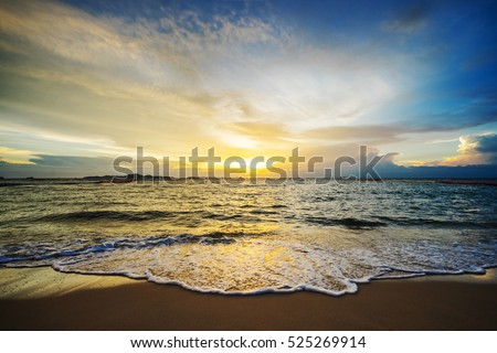 Sunset at sea with golden light shines on the surface.