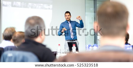 Business man making a presentation at office. Business executive delivering a presentation to his colleagues during meeting or in-house business training, explaining business plans to his employees. Royalty-Free Stock Photo #525323518