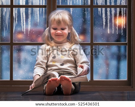 Little happy child reading a book. A large picture window. Outside the window, snow falls, winter. The house is warm, the girl barefoot