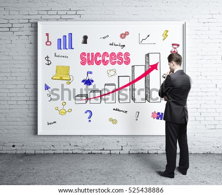 Back view of thoughtful young man looking at whiteboard with creative business sketch hanging on white brick wall. Success concept #525438886
