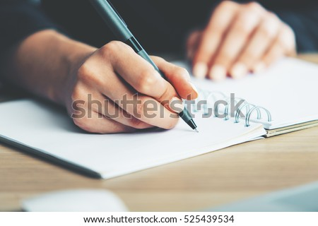 Close up of woman's hands writing in spiral notepad placed on wooden desktop with various items #525439534