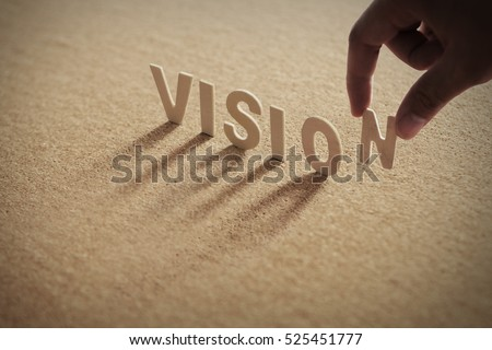 VISION wood word on compressed board with human's finger at N letter Royalty-Free Stock Photo #525451777