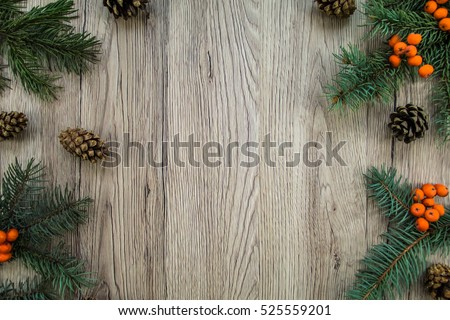 Christmas wooden background with natural decoration: fir tree, cones and rowanberries. Rustic wooden background, view from above. Flat lay, top view #525559201