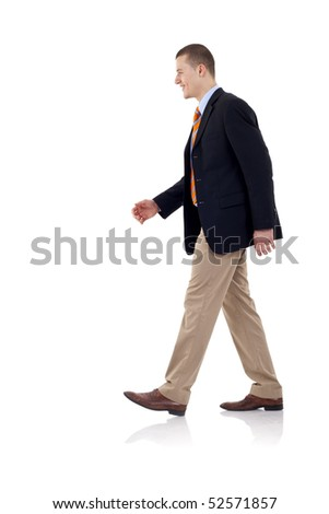 A young businessman is walking. He is smiling and looking away from the camera. isolated over white background #52571857