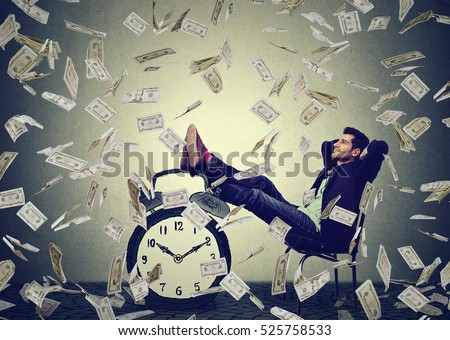 Happy young business man relaxing sitting in his office under money rain making dollar bills cash falling down. Stress free time management good earnings profit concept