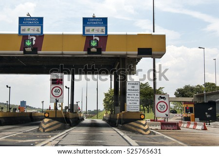 Sao Paulo, Brazil - November, 26th 2016: Highway toll plaza and speed limit, view of automatic paying lanes called in Portuguese Sem Parar, which means non-stop. #525765631