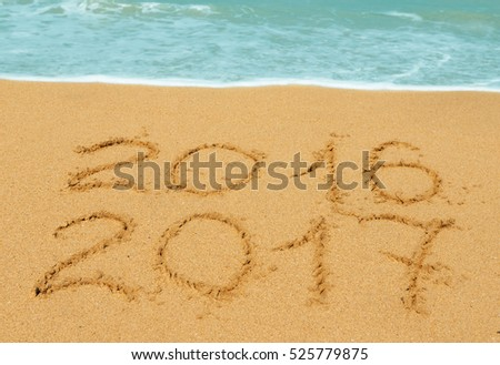 digits  2016 and 2017 on the beach - concept of new year and passing of time #525779875