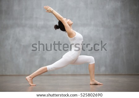 Side view portrait of beautiful young woman wearing white tank top working out against grey wall, doing yoga or pilates exercise. Standing in Warrior one pose, Virabhadrasana. Full length Royalty-Free Stock Photo #525802690