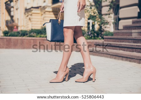 Close up of slim legs of woman wearing high heel shoes. Royalty-Free Stock Photo #525806443