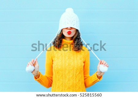 Happy cool girl blowing red lips makes air kiss wearing a knitted hat, yellow sweater over blue background #525815560