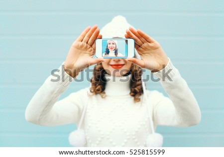 Happy pretty girl taking photo self portrait on smartphone over blue background in winter knitted clothes