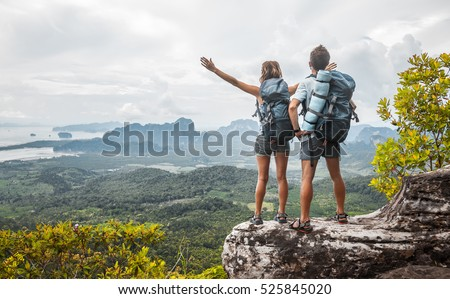 Hikers with backpacks relaxing on top of a mountain and enjoying the view of valley Royalty-Free Stock Photo #525845020