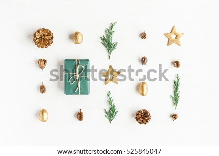 Christmas composition. Gift, christmas golden decorations, cypress branches, pine cones on white background. Flat lay, top view Royalty-Free Stock Photo #525845047