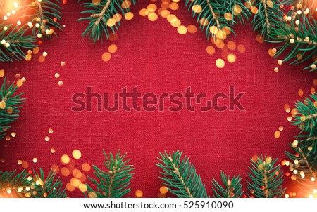 Christmas background with xmas tree and sparkle bokeh lights on red canvas background. Merry christmas card. Winter holiday theme. Happy New Year. Space for text Royalty-Free Stock Photo #525910090