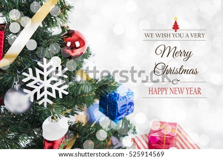 Christmas decorative with gift box and snowflake on christmas tree and Merry Christmas and Happy New Year 2017 text on bokeh light background. #525914569