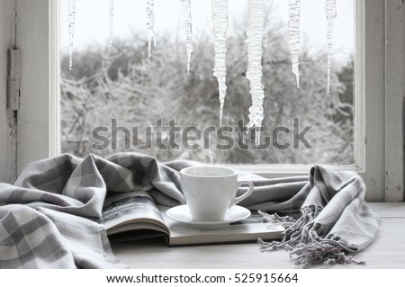 Cozy winter still life: cup of hot coffee and opened book with warm plaid on vintage windowsill against frozen big icicles from outside.. Royalty-Free Stock Photo #525915664