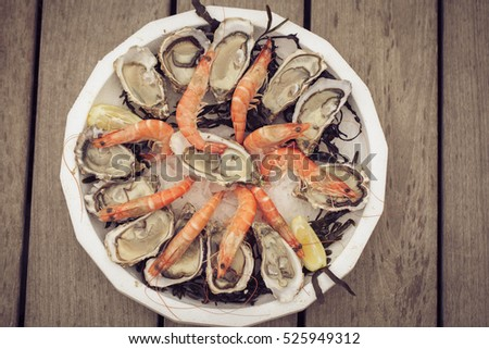 Plate with seafood - oysters and shrimps on wooden background. Toned with sepia boho style colors. Seafood concept.  #525949312