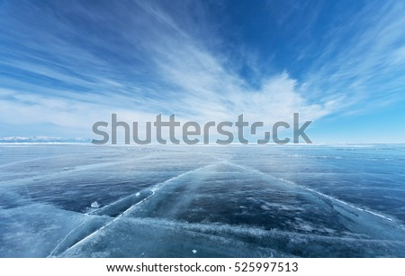 Frozen Lake Baikal. Beautiful stratus clouds over the ice surface on a frosty day. Natural background Royalty-Free Stock Photo #525997513