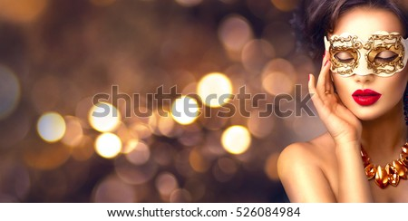 Beauty model woman wearing venetian masquerade carnival mask at party over holiday dark background with magic glow. Christmas and New Year celebration. Glamour lady with perfect make up and hairstyle #526084984