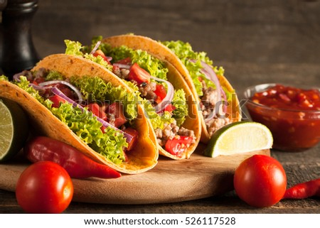 Photo of Mexican tacos with ground beef, onion, tomatoes, chili, red sauce, lettuce and lime on wooden background. Spicy and fast food concept. #526117528
