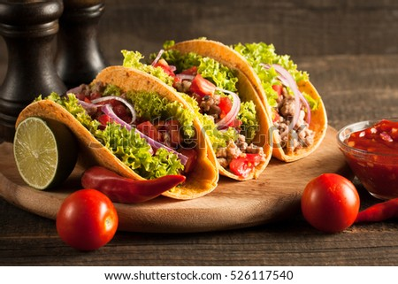 Photo of Mexican tacos with ground beef, onion, tomatoes, chili, red sauce, lettuce and lime on wooden background. Spicy and fast food concept. #526117540