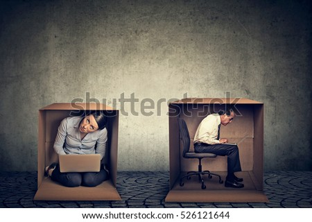Introverts. Man and woman sitting inside different boxes working on laptop computer