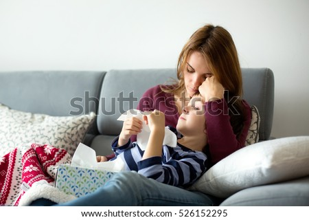 Young mother, holding her little sick boy, lying together on the couch #526152295