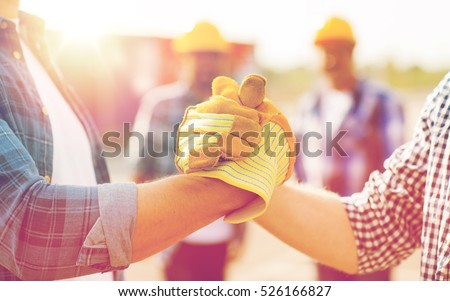 building, teamwork, partnership, gesture and people concept - close up of builders hands in gloves greeting each other with handshake on construction site Royalty-Free Stock Photo #526166827