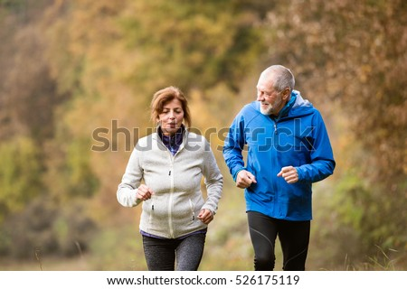 Beautiful senior couple running outside in sunny autumn forest #526175119