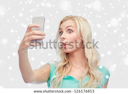 technology, winter holidays, christmas, fun and people concept - funny young woman or teenage girl taking selfie with smartphone and making fish face over snow