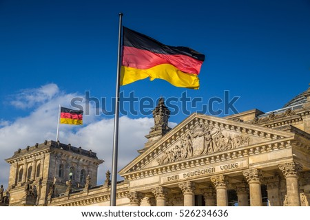 German flags waving in the wind at famous Reichstag building, seat of the German Parliament (Deutscher Bundestag), on a sunny day with blue sky and clouds, central Berlin Mitte district, Germany Royalty-Free Stock Photo #526234636