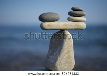 Stones pile background. Scales balance. Balanced stones on the top of boulder. To weight pros and cons. Balance of stones on a blue sky background with a copy space. #526261333